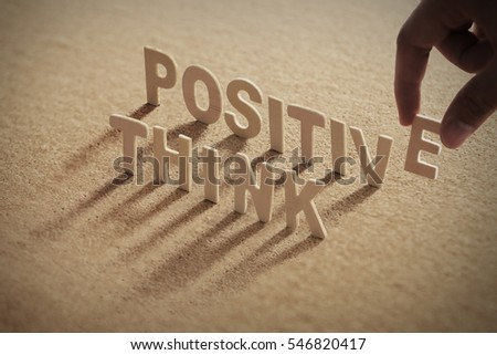 THINK POSITIVE wood word on compressed or cork board with human's finger at E letter.  #546820417