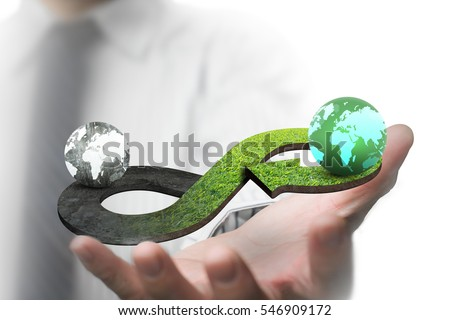 Green circular economy concept. Man's hand showing arrow infinity symbol with grass texture and two globes of different colors. #546909172