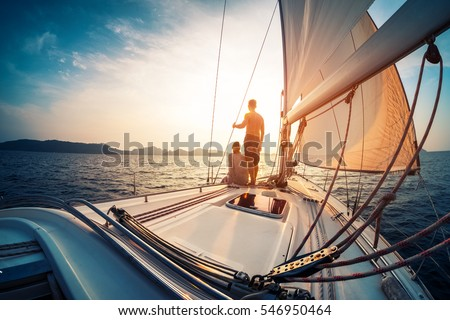 Couple enjoying sunset from the deck of the sailing boat moving in a sea #546950464