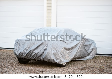 Sports car under silver colored cover outside a closed garage. Royalty-Free Stock Photo #547044322