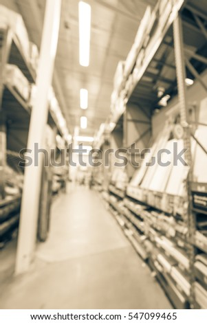 Blurred a large hardware store. Defocused interior of home improvement retailer with aisles, shelves, racks of tool for house repair from floor to ceiling. Inventory, wholesale concept. Vintage tone. #547099465