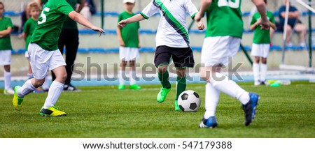 Young Boys Playing Soccer Football Match on Pitch. Kids Running and Kicking Soccer Ball on Green Grass. Soccer Children Game #547179388