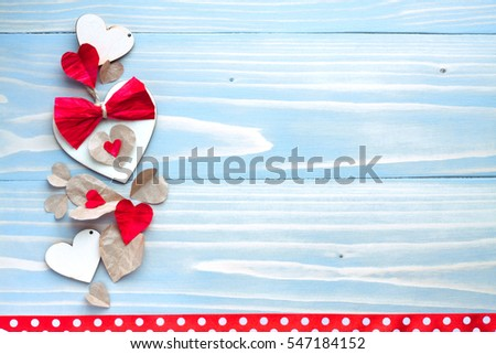 Happy Valentines day photo card background. Blue wooden table and natural material hearts with red bows hipsters background birthday women's day party celebrations decor objects cute polka dots ribbon