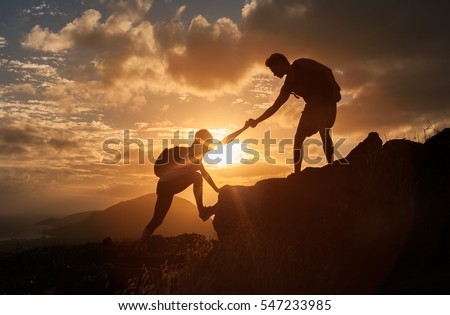 Male and female hikers climbing up mountain cliff and one of them giving helping hand.  People helping and, team work concept.   Royalty-Free Stock Photo #547233985
