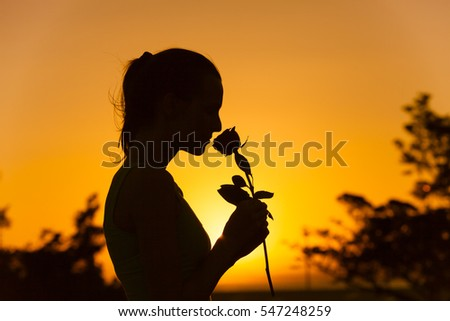 Silhouette of woman smelling a rose.