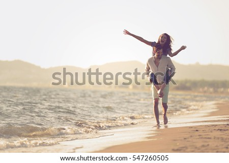 A guy carrying a girl on his back, at the beach, outdoors Royalty-Free Stock Photo #547260505