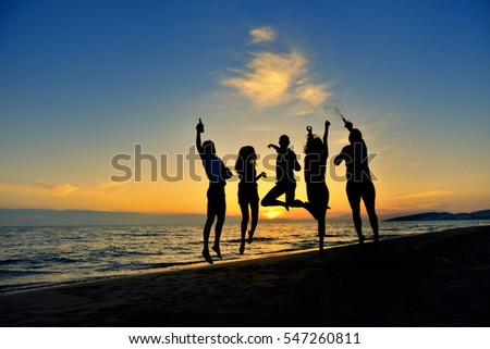 group of happy young people dancing at the beach on beautiful summer sunset #547260811
