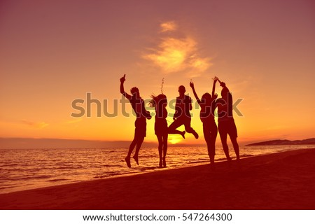 group of happy young people dancing at the beach on beautiful summer sunset #547264300