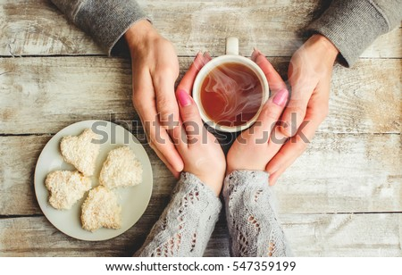 tea lovers ' hands. On wooden background.