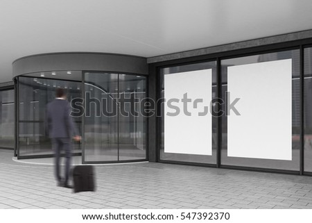 Rear view of a businessman with luggage entering a building with glass doors and two big posters. 3d rendering. Mock up