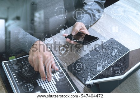 businessman hand using smart phone,mobile payments online shopping,omni channel,digital tablet docking keyboard computer,documents,in modern office on wooden desk,virtual interface icons screen #547404472
