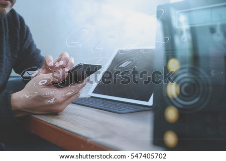 businessman hand using smart phone,mobile payments online shopping,omni channel,digital tablet docking keyboard computer,compact server on wooden desk,virtual interface icons screen #547405702