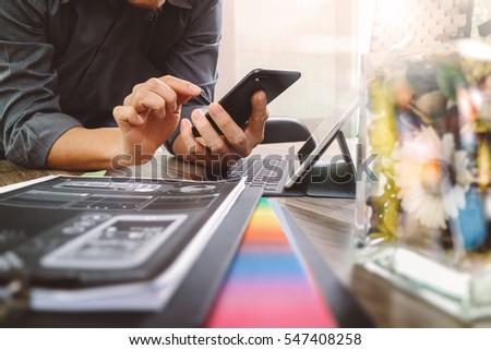 businessman hand using smart phone,mobile payments online shopping,omni channel,digital tablet docking keyboard computer,flower glass vase on wooden desk,filter #547408258