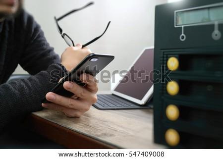 businessman hand using smart phone,mobile payments online shopping,omni channel,digital tablet docking keyboard computer,compact server on wooden desk #547409008