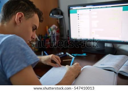 Teenager boy doing homework on his desk at home #547410013