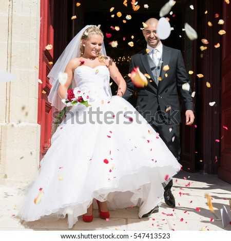 Just married couple under a rain of rose petals #547413523