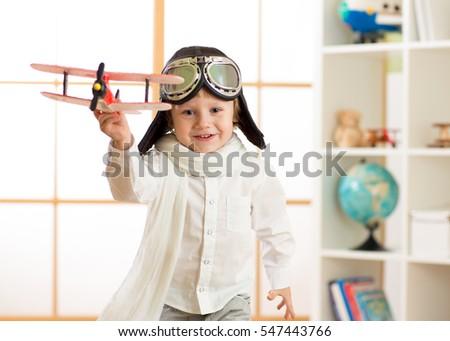 happy kid boy play in airplane indoors #547443766