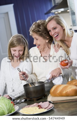 Grandmother with family cooking in kitchen, smiling and laughing together #54744949
