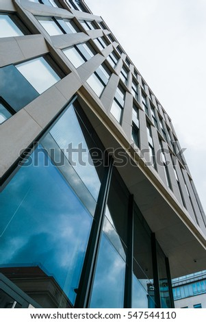 Low angle perspective of a modern high-rise office building with tall glass windows reflecting the sky #547544110