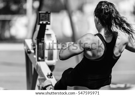 Female athlete on rowing machine on cross competition. Royalty-Free Stock Photo #547595971