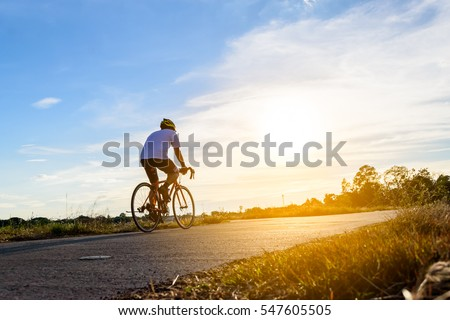 A man ride on bike on the road. Sport and active life concept sunset time. A man riding on  bicycle in a park. Blue sky with orange sun beam over the body of cyclist.  Royalty-Free Stock Photo #547605505