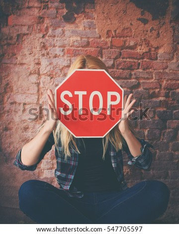 A young girl is holding a stop sign to her face for a concept of violence, hate or texting while driving.