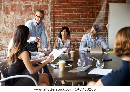 Businesspeople Meeting In Modern Boardroom Through Glass Royalty-Free Stock Photo #547750285