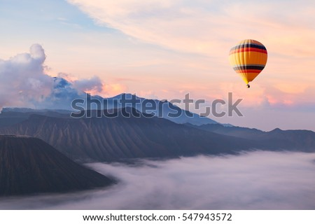 beautiful inspirational landscape with hot air balloon flying in the sky, travel destination Royalty-Free Stock Photo #547943572