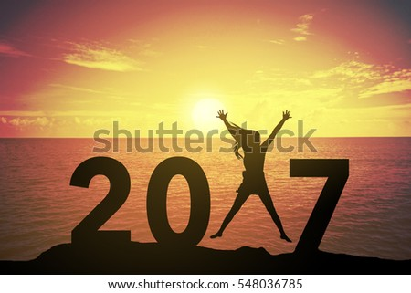 Silhouette young woman standing and raising up her hand about happy concept on at 2017 over a beautiful sunset or sunrise at the sea. background for happy new years. success in 2017 years #548036785