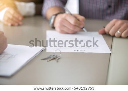 Close up of young people got access to home ownership signing a bank loaning, mortgage program, bound with a loan, buying a home as a good option, couple meeting with bank worker or real estate agent #548132953