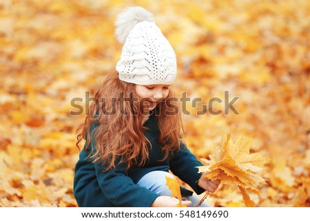 Cute little girl gathering bouquet of leaves in autumn park #548149690