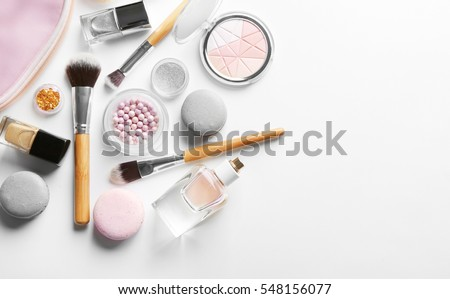 Makeup products with cosmetic bag and macaroons on light background Royalty-Free Stock Photo #548156077