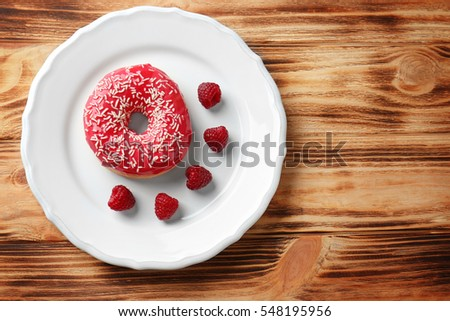 Plate with delicious donut and berries on wooden background #548195956