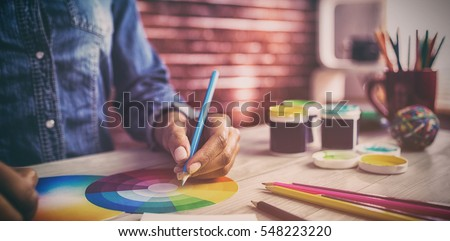 Graphic designer drawing on colour chart at workplace