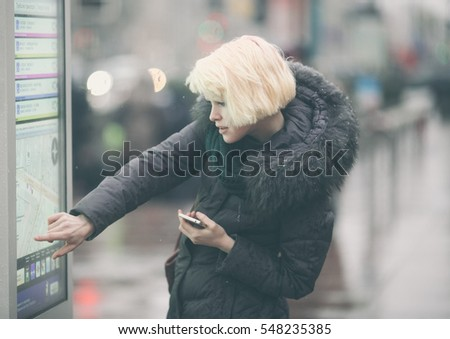 Young beautiful woman tourist using modern digital display board information, cute female watching movement of buses on electronic bulletin board in urban city #548235385