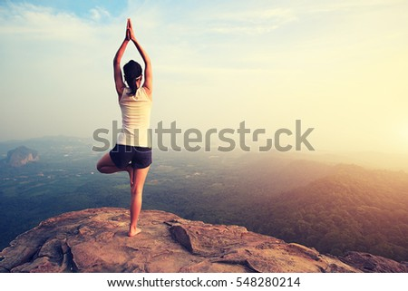 young fitness woman practice yoga at mountain peak cliff #548280214