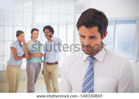 Colleagues gossiping with sad young businessman in foreground at a bright office Royalty-Free Stock Photo #548330869