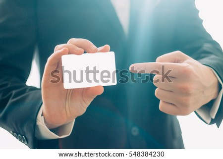 Businessman holding blank visit card and pointing. #548384230