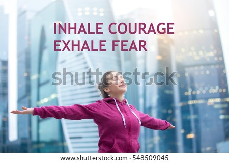 """Sporty healthy model wearing pink hoody, feeling alive with arms outstretched to sky, closed eyes, enjoying bliss, fresh air. Photo with motivational text """"Inhale courage, exhale fear"""""""