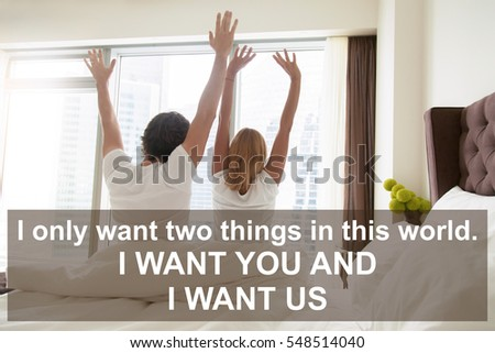 """Back view of young happy couple, sitting on bed, looking through window at big city scenery. Photo with motivational text """"I only want two things in this world. I want you and I want us"""""""