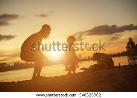 Silhouettes of mother and little daughter walking at sunset #548528902