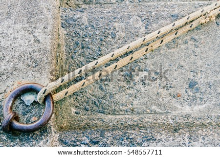 Iron ring with rope tied and concrete background on a dock #548557711