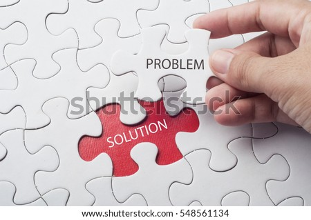 Hand holding piece of jigsaw puzzle with word problem & solution. Royalty-Free Stock Photo #548561134