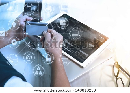 young man shopping on line with smart phone is listening music with headphones is holding a credit card on his hand at home,Social distancing and Working from home concept. #548813230