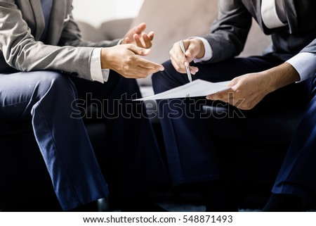 Image of two young businessmen discussing project at meeting Royalty-Free Stock Photo #548871493