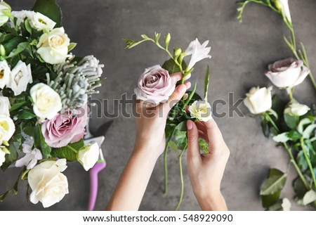 Female florist making beautiful bouquet at flower shop Royalty-Free Stock Photo #548929090