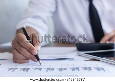 Businessman working on office desk, Watching something on Calculator, He was thinking about something for idea and make a Note something of Idea, Blurred background, Business concept. #548946397