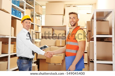 Two businessmen shaking hands at warehouse #549045400