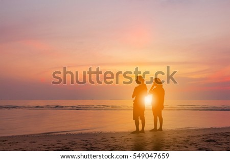 Silhouette of Happy family with little daughter watched together sunset evening sky at beach background, Life and Happiness concept. #549047659