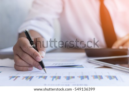 Businessman working on office desk, Watching something on Calculator. He was thinking about something for idea and make a Note something of Idea, Blurred background, Business concept. #549136399